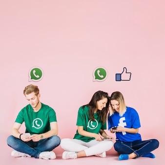Iconos de redes sociales sobre grupo de amigos que usan teléfono móvil