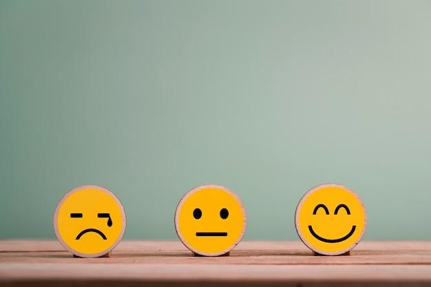 Iconos de emoticonos de cara de sonrisa feliz en cubo de madera