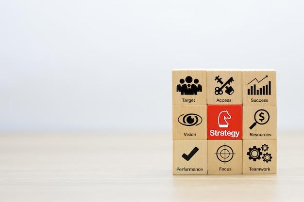 Iconos gráficos de estrategia y planificación para el éxito empresarial en bloques de madera