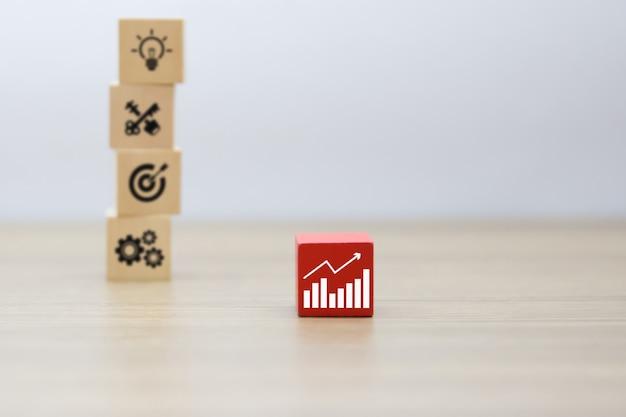 Iconos de gráficos de negocios en bloques de madera.