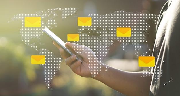 Iconos de mensaje de mapa mundial con mano de hombre usando smartphone