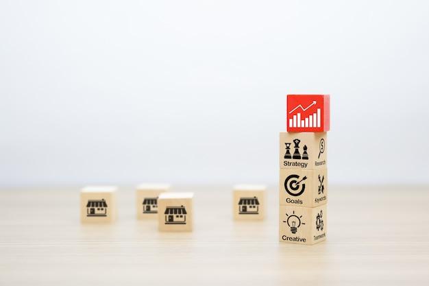 Iconos de negocios en forma de cubo de madera apilados.