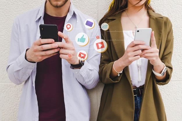 Iconos de notificación móvil entre hombre y mujer usando teléfono celular