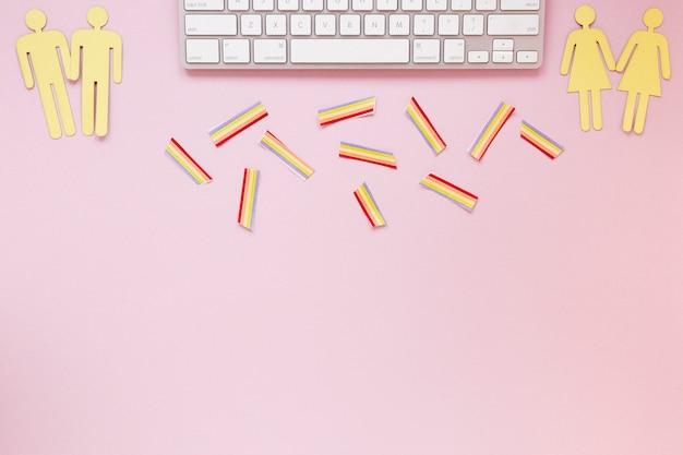 Iconos de parejas homosexuales con arco iris de papel y teclado.