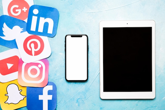 Iconos de redes sociales con teléfono celular y tableta digital en pared pintada de azul