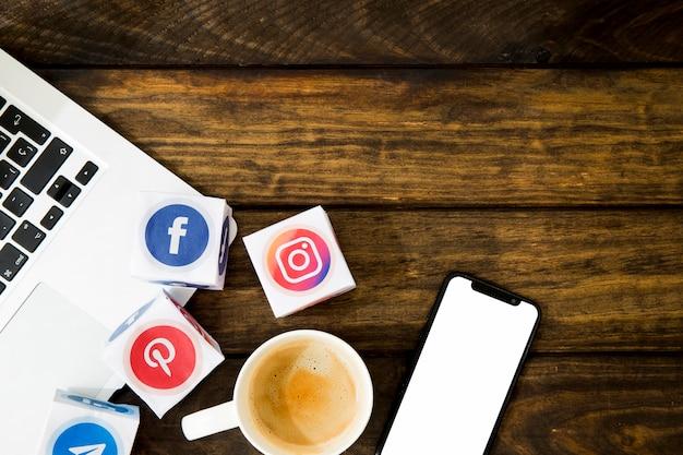 Iconos de redes y taza de café con artilugios electrónicos