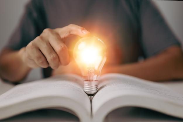 Idea de aprender conocimientos en clase en línea o elearning en casa bombilla incandescente y libro