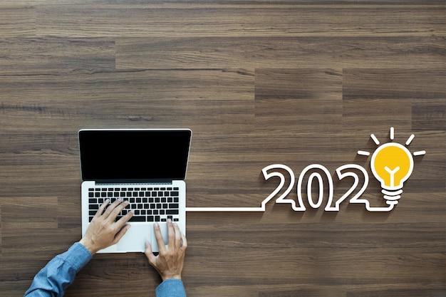 Idea creativa bombilla 2020 con empresario trabajando en la computadora portátil