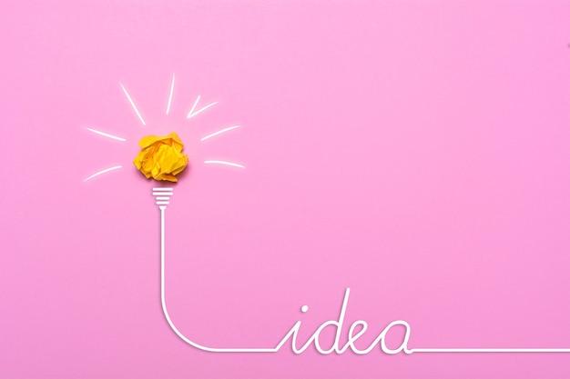 Idea creativa de papel arrugado. una bombilla encendida sobre un fondo rosa. concepto de educación.