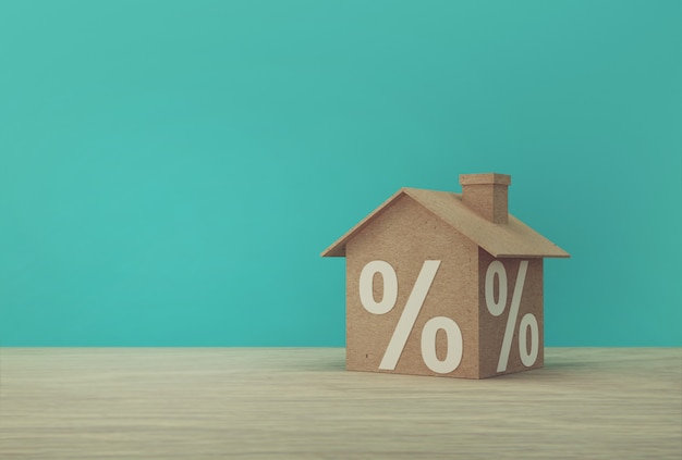 Idea creativa de papel modelo de casa y el icono de símbolo de signo de porcentaje en la mesa de madera. concepto de inversión inmobiliaria propiedad hipotecaria y vivienda.