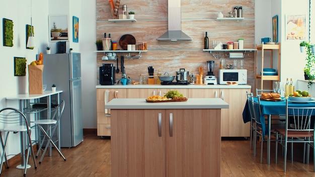 Idea de decorar una cocina moderna de espacio abierto. comedor preparado para cena familiar, diseño de arquitectura de lujo con decoración residencial con mesa de comedor en el medio de la sala.