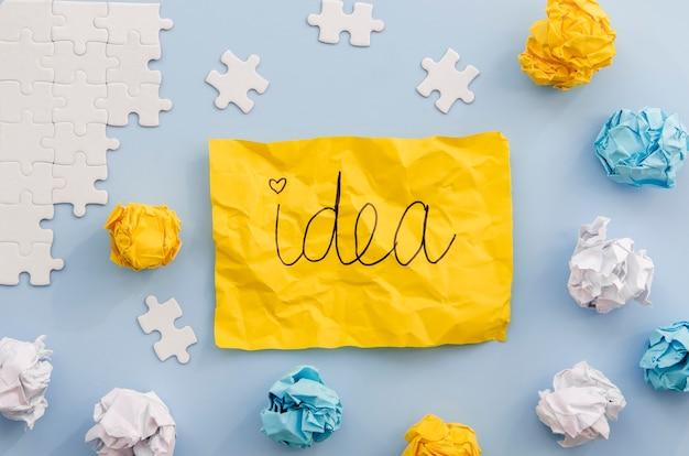 Idea escrita en un papel amarillo con piezas de rompecabezas