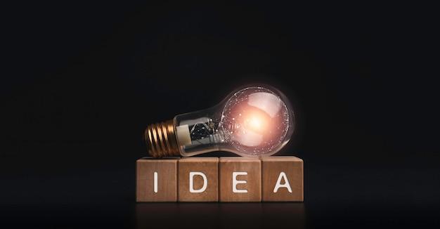 Idea, palabras en bloques de cubo de madera con lámpara eléctrica bombilla incandescente sobre fondo oscuro. banner de concepto de idea creativa.