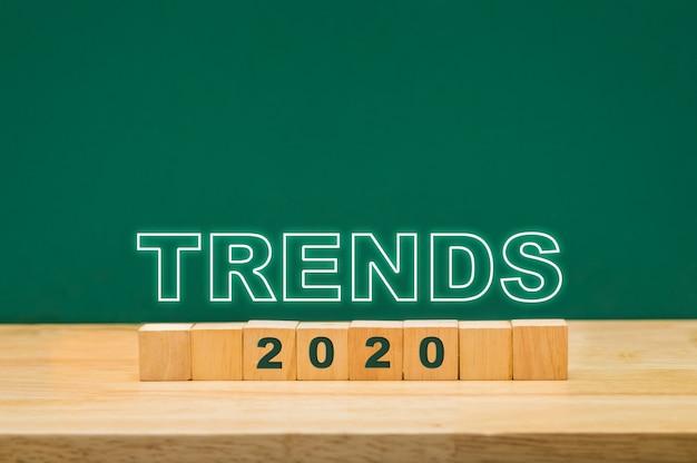 Idea de tendencias 2020 en bloque de cubo de madera sobre mesa con pizarra verde
