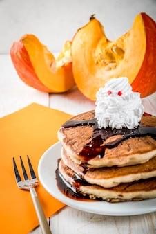 Ideas para el desayuno de los niños, golosinas para acción de gracias y halloween. panqueques con salsa de chocolate y crema batida en forma de fantasma. sobre una mesa de madera blanca, copyspace
