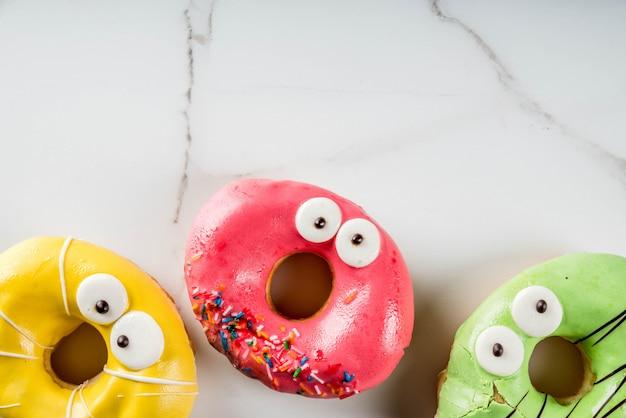 Ideas para niños trata en halloween. donuts de colores en forma de monstruos con ojos, verde, amarillo,