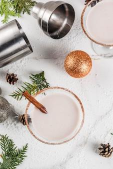 Ideas y recetas para bebidas navideñas. rompope martini, con palitos de canela, sobre mesa de mármol blanco con decoración navideña, vista superior
