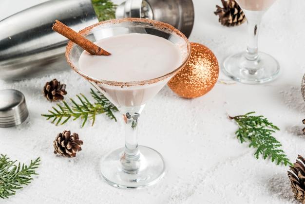 Ideas y recetas para bebidas navideñas. rompope martini, con palitos de canela, sobre mesa de mármol blanco con decoración navideña,