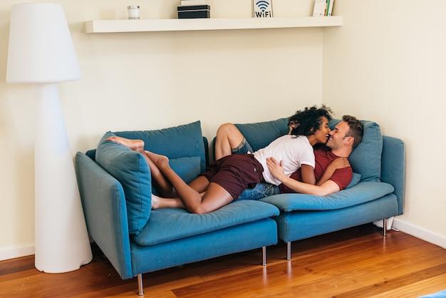 Idílica pareja multiétnica disfrutando mutuamente en el sofá en casa