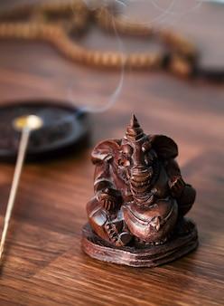 Ídolo de ganesha de madera sobre la mesa con varitas de incienso