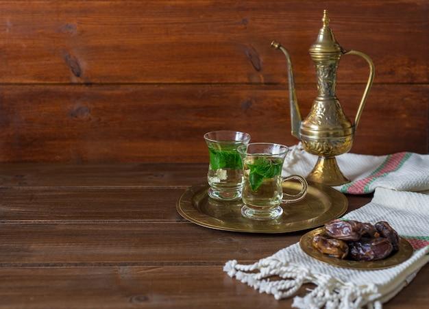 Iftar y suhoor ramadan concept, té de mentha en tazas de vidrio y dátiles en madera con una tetera antigua