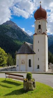 Iglesia en los alpes montañas sol hierba nubes
