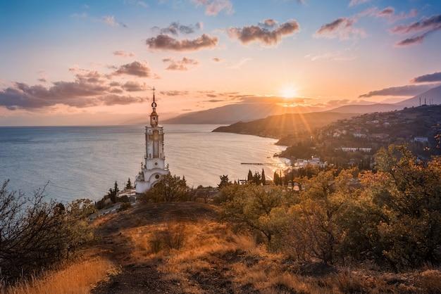 Iglesia del faro al atardecer. costa del mar negro.