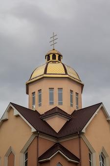 Iglesia ortodoxa de cúpulas doradas con cruz contra el cielo azul
