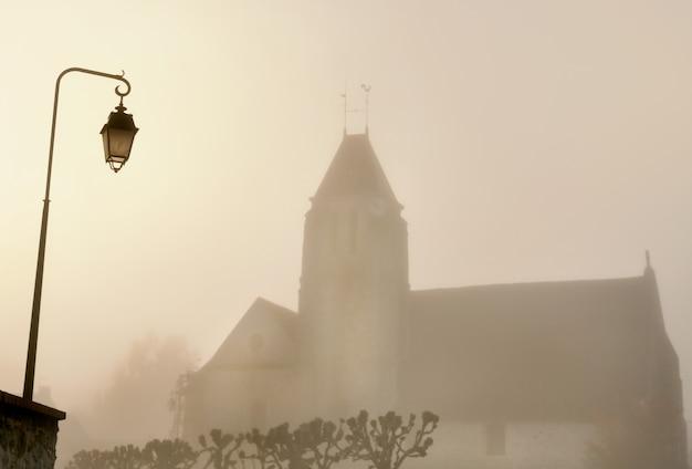 Iglesia de un pueblo y una farola en la niebla