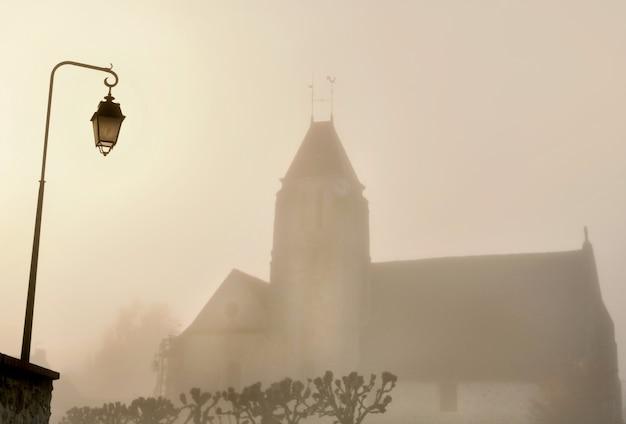 Iglesia de un pueblo francés rural y una farola en la niebla