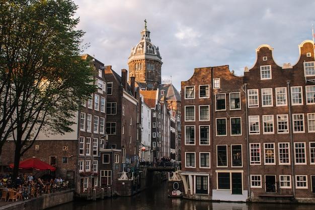 Iglesia de san nicolás dominando el canal principal del barrio rojo en el centro de amsterdam, holanda, países bajos.