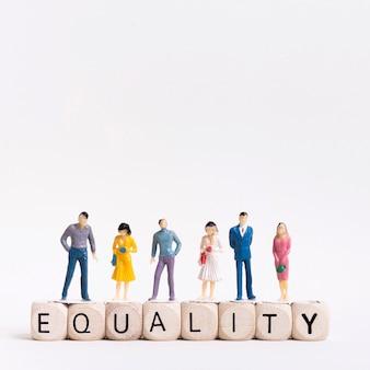 Igualdad escrita en cubos de madera y personas arriba