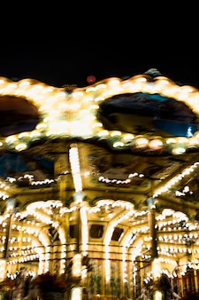 La iluminación borrosa del carrusel gira en el parque de diversiones en la noche