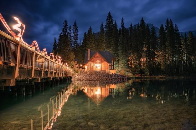 Iluminación de la casa de madera con puente de madera sobre el lago esmeralda en el parque nacional yoho