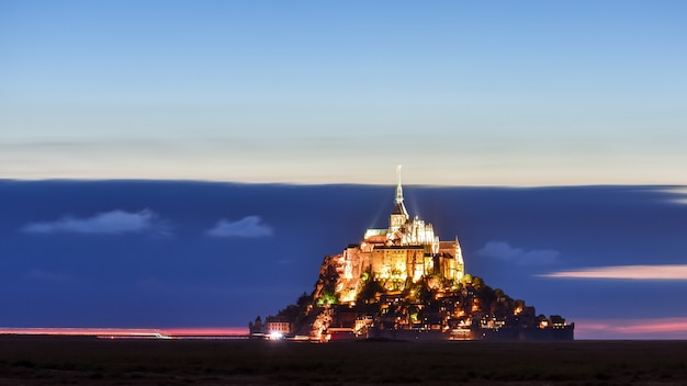Iluminado mont saint michel al atardecer en un cielo colorido