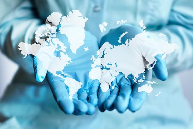 Imagen abstracta del mapa mundial en manos del médico en guantes médicos.