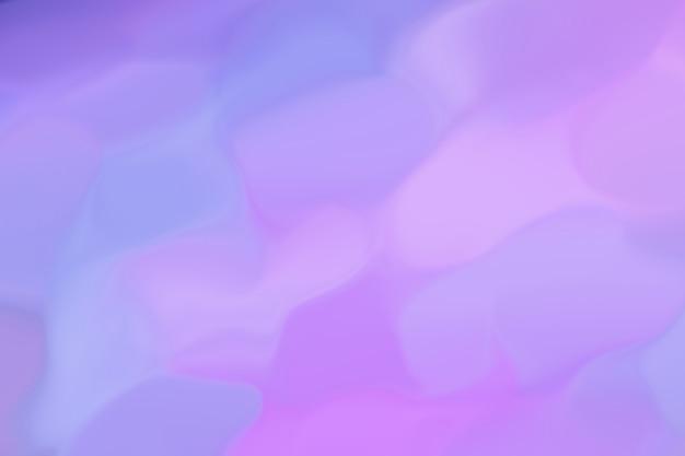La imagen abstracta resplandece de diferentes colores de azul a rosa y lila. patrón de fondo desenfocado. ultramarino combinado con luz de neón. estilo retro de los 80