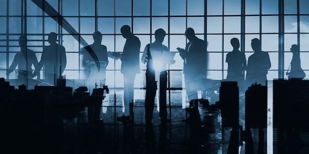 Imagen abstracta de la silueta de la gente de negocios en la ventana de cristal