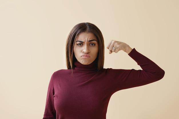 Imagen aislada de atractiva joven elegante mujer de piel oscura con cabello suelto con mirada furiosa loca, haciendo muecas y sosteniendo el puño bombeado frente a ella, lista para golpear. feminismo y poder femenino