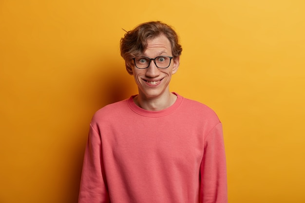 Imagen aislada de chico hipster positivo tiene una reacción feliz en noticias recientes, está de buen humor, se ve sorprendentemente a través de gafas, usa un jersey rosa casual, aislado en una pared amarilla. verdaderas emociones humanas