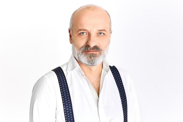 Imagen aislada de hombre senior de moda atractivo con barba gris gruesa mirando a la cámara con sonrisa de confianza, vestido con camisa blanca y tirantes