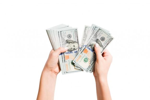 Imagen aislada de las manos femeninas que cuentan dólares en la pared blanca. vista superior del concepto de sueldos y salarios