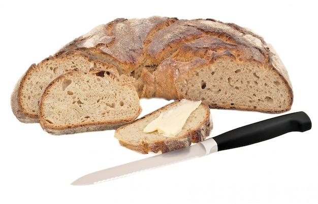 Imagen aislada de pan con granos; pan y mantequilla y un cuchillo