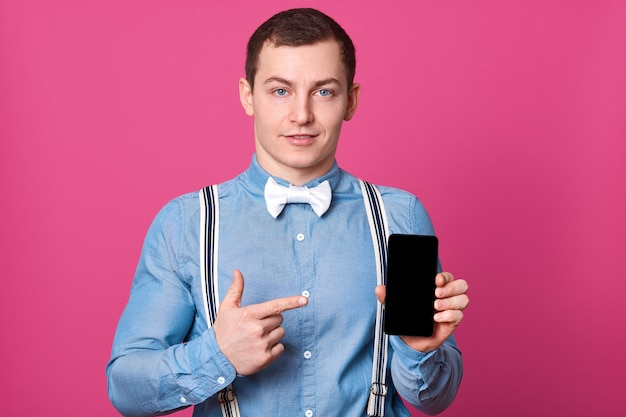 Imagen de un alegre joven vestido con una camiseta azul, tirantes y corbatín blanco, de pie sobre la pared rosada que muestra la pantalla de su teléfono y apuntando con el dedo índice. copia espacio