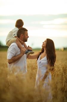 Imagen de alegre mamá caucásica, papá y su hijo se divierten juntos y sonrisas en el campo