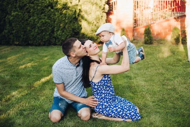 Imagen de alegre mamá caucásica, papá y su hijo se divierten juntos y sonrisas en el jardín