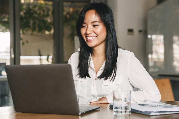 Imagen de alegre trabajadora asiática de 20 años con camisa blanca sonriendo mientras está sentado a la mesa en la oficina y trabajando en la computadora portátil