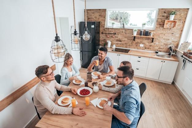 Imagen de alto ángulo de cinco amigos o compañeros de cuarto multiétnicos comiendo panqueques caseros.