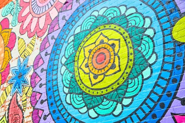 Imagen del ángulo de la pared de ladrillo graffiti coloridas flores de arco iris