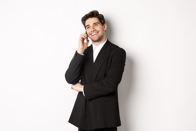 Imagen de apuesto y exitoso hombre de negocios hablando por teléfono, sonriendo complacido, de pie en traje contra el fondo blanco.